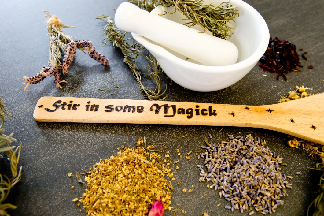 Stir in some Magick - wooden stirrer with dried Herbs on gray / grey slate background